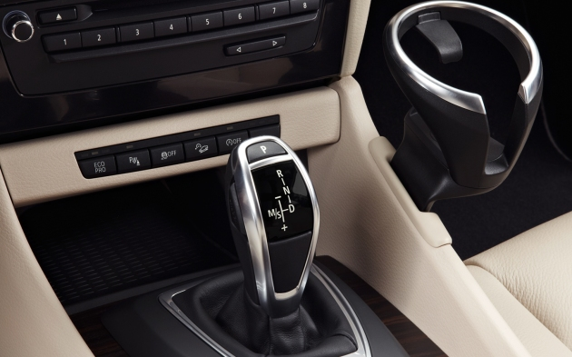 BMW's electronic shifter - found in most new BMWs - is easy to use once you get used to it. Note the third swing-out cup holder for either the passenger or driver. It's right in the way of the passenger's knee. It's beautifully-engineered, but not terribly sturdy.