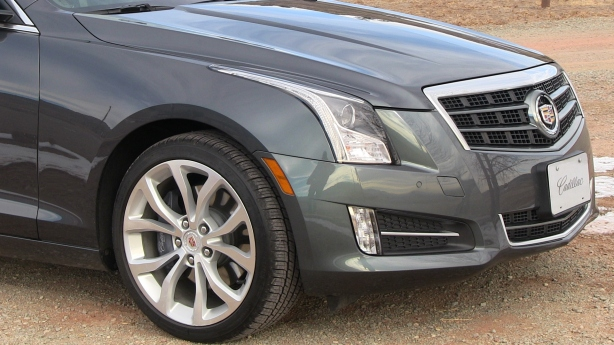Detail of the 2013 Cadillac ATS'  headlight module. Note how the vertical LED running lights sweep up and over the front wheel fender. A nice touch.