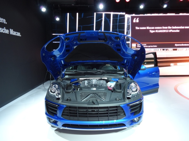 Here is the 2015 Porsche Macan, nearly naked with its standard 3.0L V6 engine showing. Note how the hood wraps around the sides, rather than just the top, of the car.