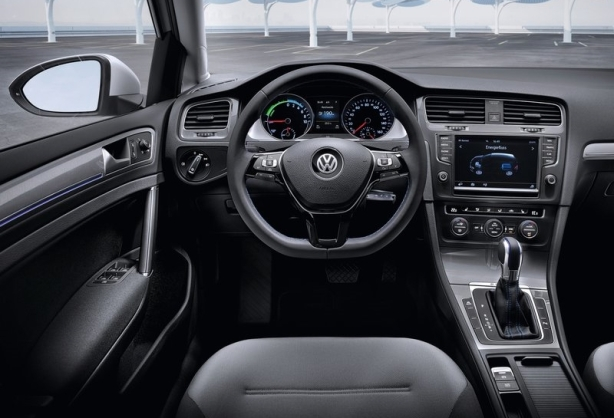 Cockpit of the 2015 e-Golf. Note the electronic parking brake in the center area and the covered cup holders.